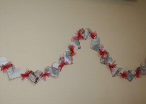 I usually pin crafts to my Pinterest board and never actually make them.  Not this time!  C.J. and I folded hearts using pages from the Pottery Barn Kids catalog and strung them together to make garland.